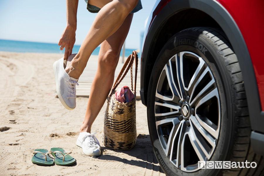 Ruota pneumatico con sfondo mare sulla sabbia, infradito, borsa e scarpe comode che sono meglio delle ciabatte quando guidi l'auto.