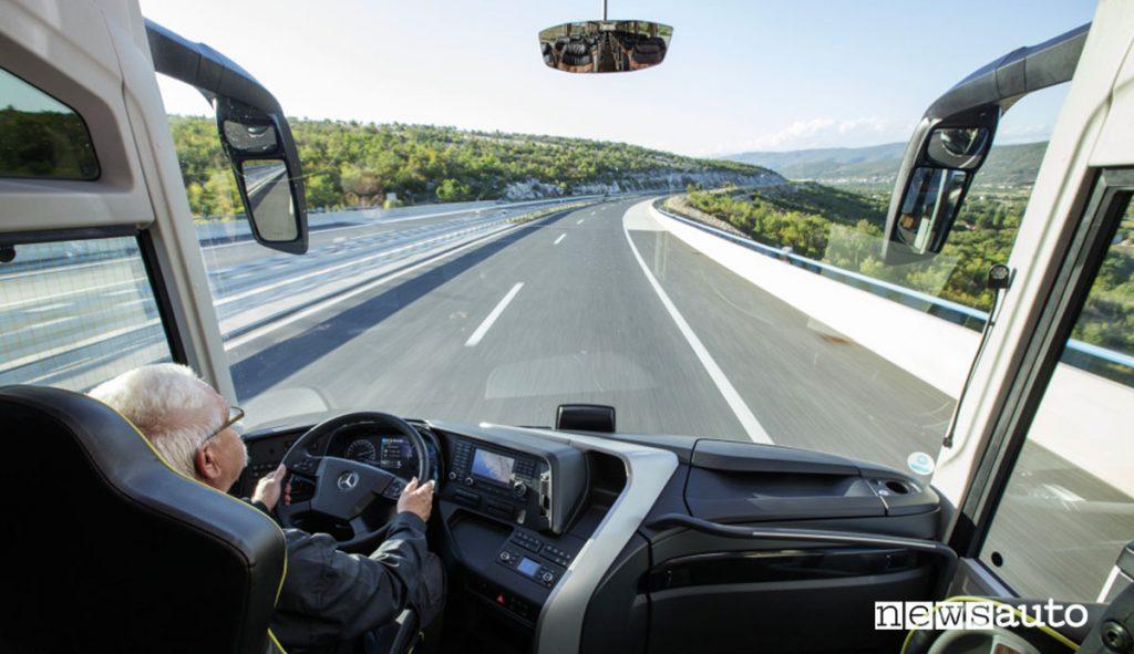 Autista alla guida di un autobus Mercedes con vetro panoramico