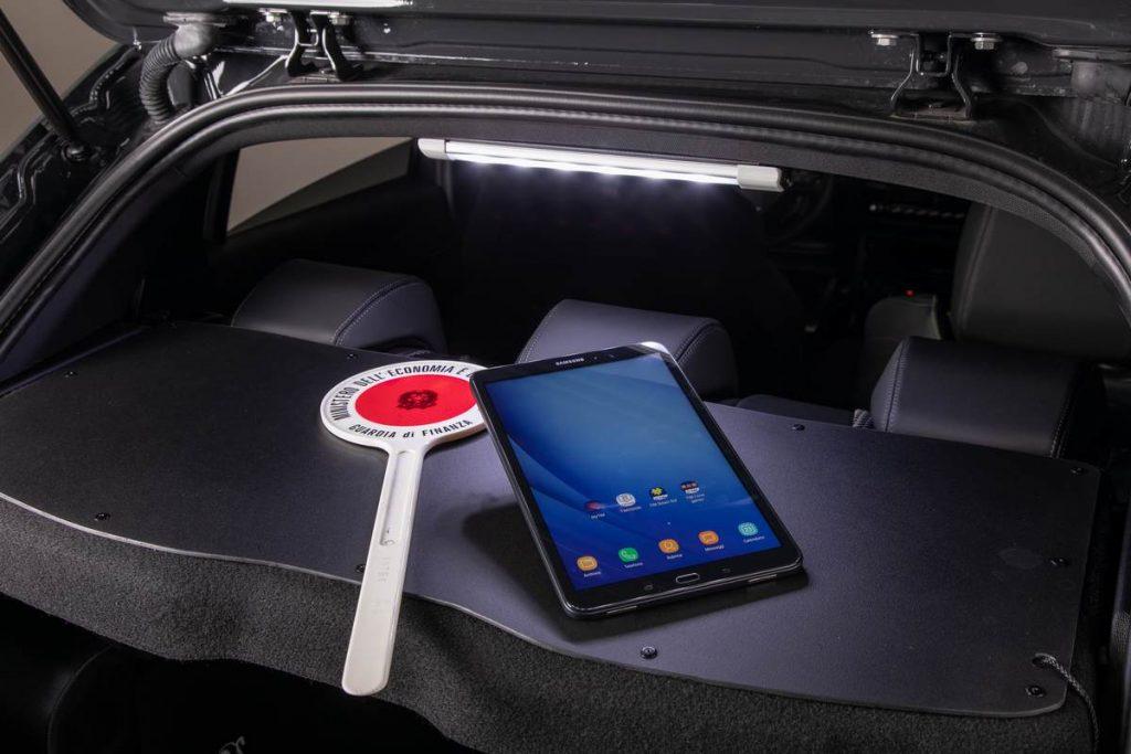 La cappelliera posteriore della Peugeot 208 è adibita a scrittoio attraverso un supporto rigido