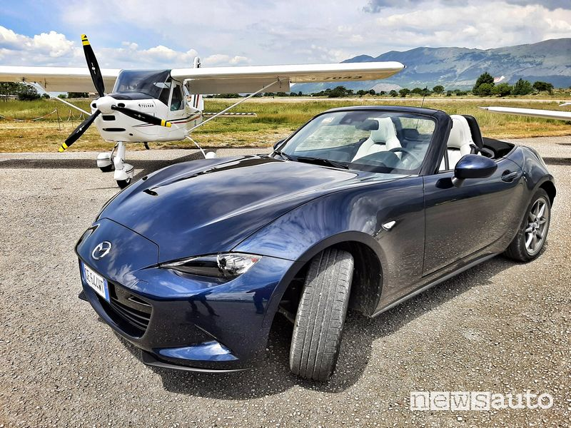 Vista di profillo Mazda MX-5 2021 a fianco di un aereo da turismo all'aero club di Celano